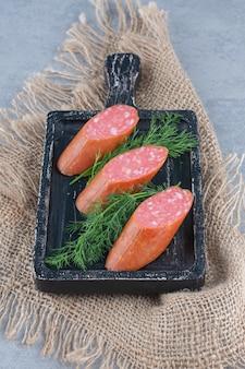 Salame de linguiça fatiada na placa de madeira com especiarias.