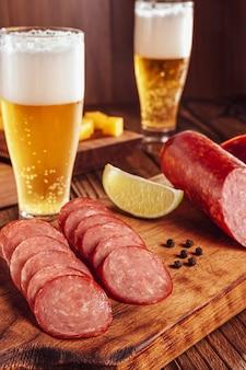 Salame defumado fatiado na tábua de cortar com dois copos de cerveja, filhotes de queijo e azeitonas