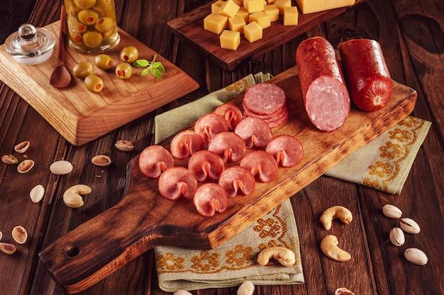 Salame defumado fatiado na tábua de cortar com filhotes de queijo, azeitonas, castanhas e pistache