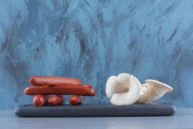 Salame e cogumelo ostra na placa de madeira.