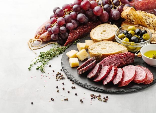 Salame fatiado em estilo rústico. salsicha de salame. salsichas diferentes com queijo, uvas e azeitona