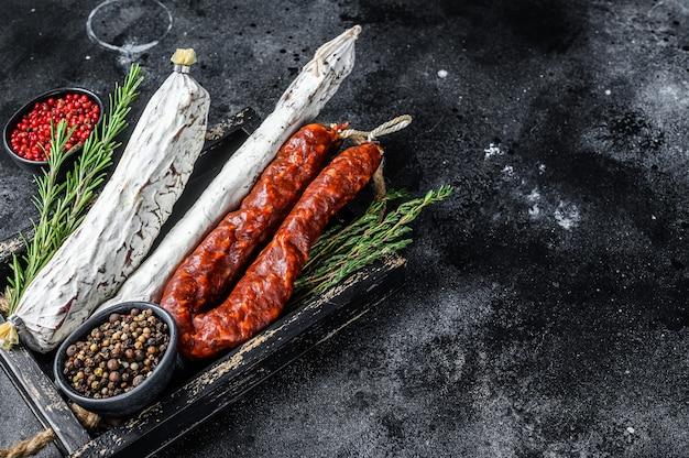 Salame, fuet e chouriço de linguiça espanhola curada a seco em bandeja de madeira