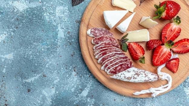 Salame fuet espanhol com queijo camembert, morangos. formato de banner longo. vista do topo.