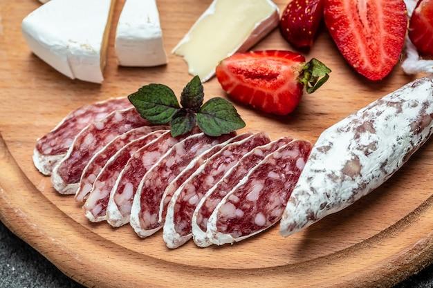 Salame fuet espanhol com queijo camembert, morangos. fundo de receita de comida. fechar-se.