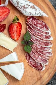 Salame fuet espanhol com queijo camembert, morangos. fundo de receita de comida. imagem vertical. vista do topo.