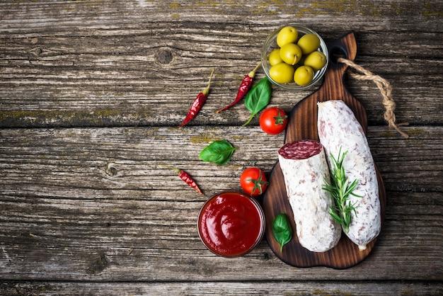 Salame italiano com alecrim, pimenta, tomate cereja e azeitonas em um fundo de madeira. bandeira. vista do topo