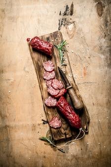 Salame perfumado com alecrim e faca velha na mesa de madeira.