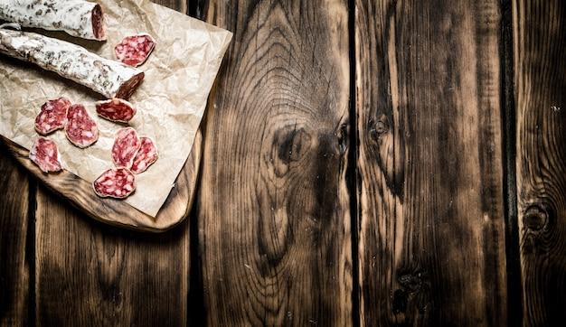 Salame picante na tábua de madeira na mesa de madeira