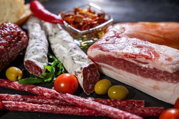 Salame, presunto fatiado, linguiça, presunto, bacon. bandeja de antepasto de carne na mesa de madeira.