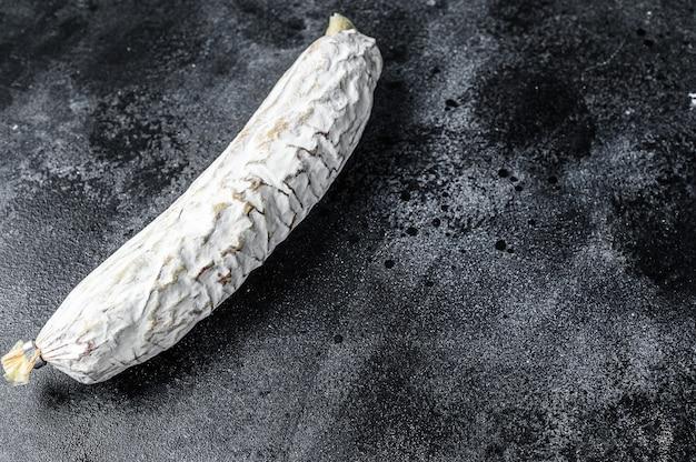 Salame salchichon curado a seco espanhol. fundo preto. vista do topo. copie o espaço.