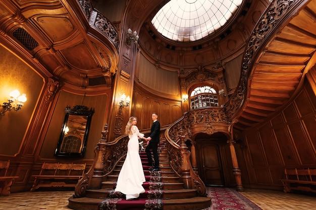 Salão chique com talha em madeira. noiva e noivo de mãos dadas e em pé na bela escada de madeira.