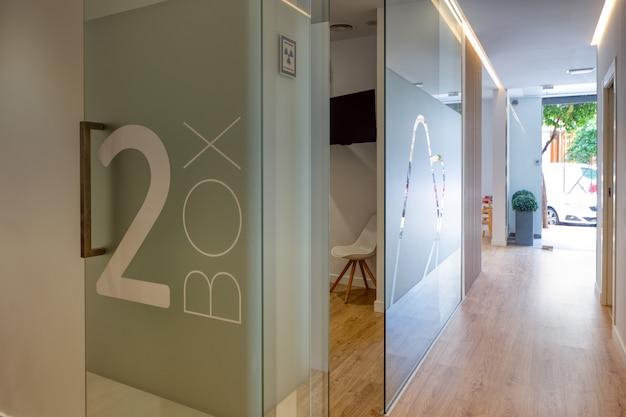 Salão da clínica odontológica moderna totalmente equipada, com mapas de vitrais e piso de madeira.