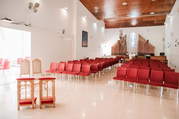 Salão da igreja católica moderna com cadeiras vermelhas e órgão