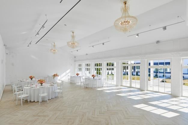 Salão de banquetes branco lindo. decoração de casamento, interior. serviço de banquetes