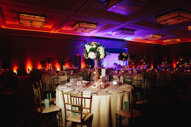 Salão de banquetes decorado com mesa redonda servida com peça central de hortênsia e cadeiras chiavari