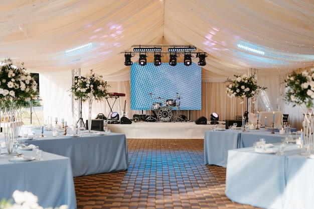 Salão de banquetes em uma tenda com toalhas de mesa e decorações azuis