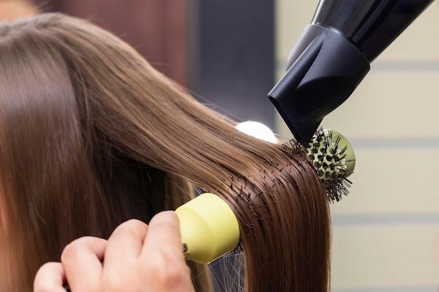 Salão de beleza feminino cabeleireiro secando o cabelo com um secador de cabelo