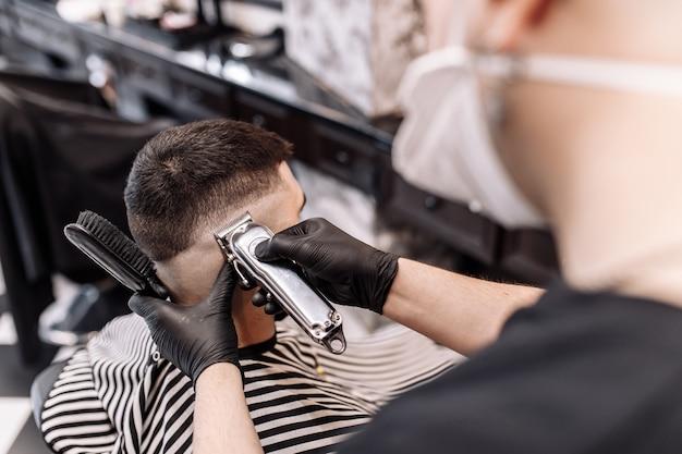 Salão de beleza masculino. corte de cabelo de homem em uma barbearia. novo estilo de corte de cabelo 2020