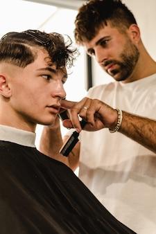 Salão de cabeleireiro para homens. barbeiro que faz o corte de cabelo na barbearia.