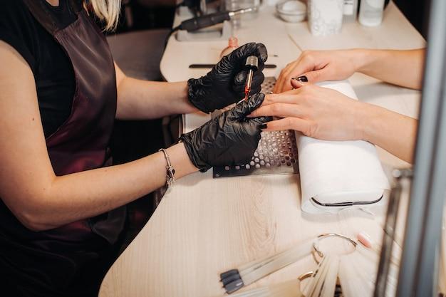 Salão de esteticista, manicure, procedimento de polimento de unhas. manicure profissional de hardware usando máquina elétrica no salão de beleza.