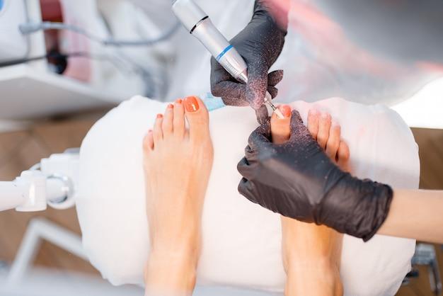 Salão de esteticista, pedicure, procedimento polonês. tratamento de unhas para cliente do sexo feminino em salão de beleza, médico em luvas trabalha com as unhas dos pés do cliente