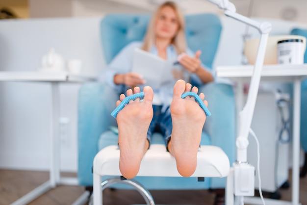 Salão de esteticista, procedimento de cuidados com os pés. tratamento de pernas para cliente em salão de beleza, cliente sentada na poltrona, relaxamento antes da pedicure
