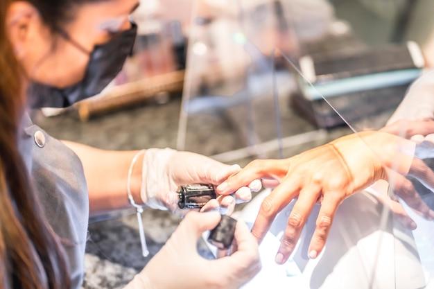 Salão de manicure e pedicure, coronavírus, covid-19, distância social. a reabertura devido à pandemia, medidas de segurança. uma trabalhadora massageando o rosto de um cliente após o tratamento com máscaras
