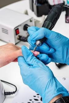 Salão de manicure, mãos do cliente e close-up mestre. tratamento de unhas com cortador