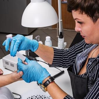 Salão de manicure, mãos do cliente e close-up mestre. tratamento de unhas com lima de manicure