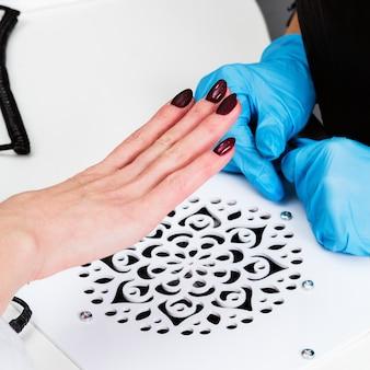 Salão de manicure, mãos do cliente e mestre, close-up