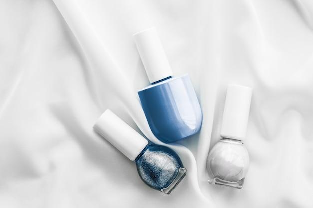 Salão de marcas cosméticas e frascos de esmalte de conceito de glamour em fundo de seda produtos de manicure francesa e cosméticos de maquiagem com esmalte para marcas de beleza de luxo e design de arte plana de férias