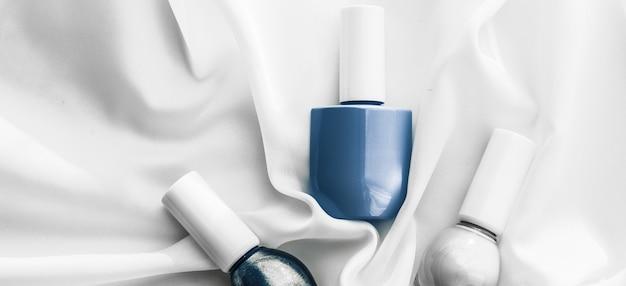 Salão de marcas cosméticas e frascos de esmalte de conceito de glamour em fundo de seda produtos de manicure francesa e cosméticos de maquiagem com esmalte para marcas de beleza de luxo e design de arte plana