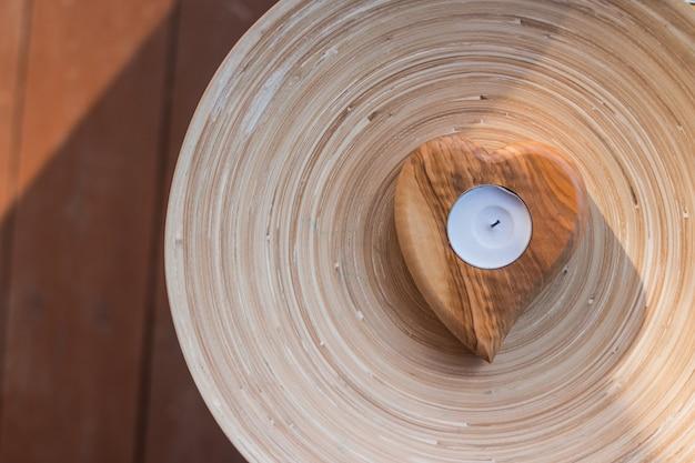 Salão de spa, tempo relaxante. pequena vela como elemento decorativo. coração de madeira. vista superior.