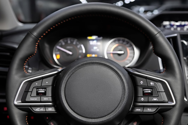 Salão de um novo carro elegante, volante, painel com velocímetro, tacômetro e outros botões de configuração