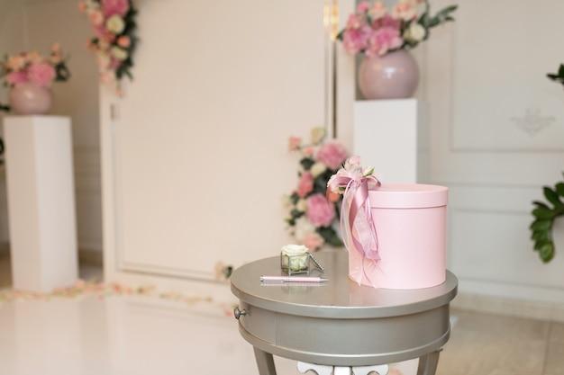 Salão do casamento. uma mesa perto do arco do casamento com um cofrinho para presentes para os noivos