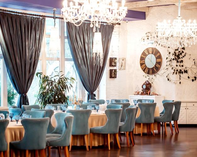 Salão do restaurante com cadeiras turquesas, paredes brancas, janelas francesas e cortinas