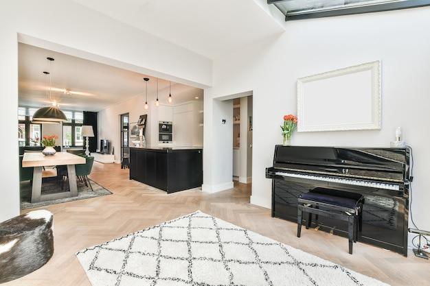 Salão espaçoso com carpete e piano localizado perto da sala de jantar em uma casa contemporânea