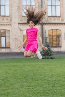 Salão que deixa o cabelo mais vital e enérgico. criança pula o verão ao ar livre. garota ativa com longos cabelos castanhos. cabeleireiro. salão de beleza. barbeiro de crianças. em cabeleireiros. cuidados com o cabelo no salão de beleza.