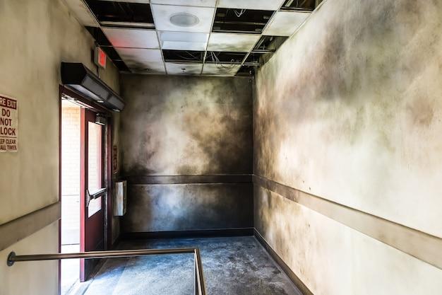 Salão queimado sombrio e saída de incêndio aberta.