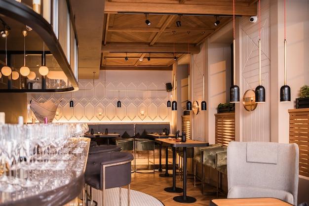 Salão semi-iluminado em estilo loft em um restaurante com cozinha aberta no espaço