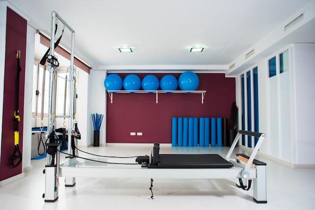 Salão vazio com equipamento moderno para treinamento de pilates