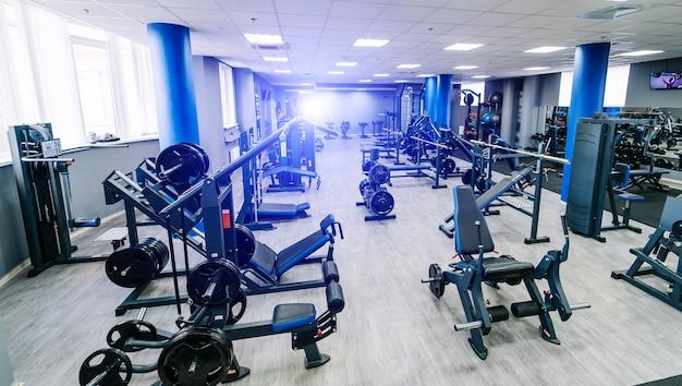 Salão vazio do centro de fitness. interior do ginásio moderno e vazio com equipamentos. equipamento de esporte diferente no ginásio moderno. fechar-se