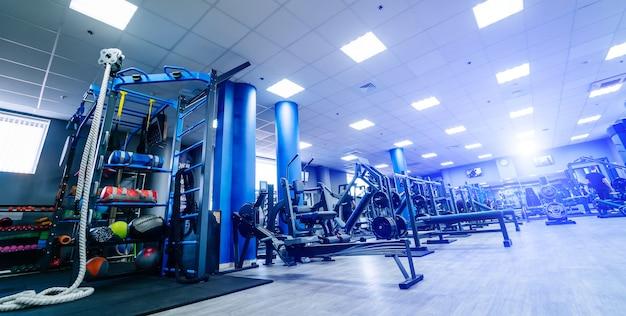 Salão vazio do centro de fitness. interior do ginásio moderno e vazio com equipamentos.