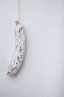Salchichon de salsicha na mesa branca.