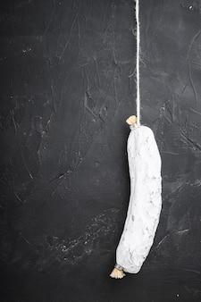 Salchichon espanhol salsicha curada seca na superfície preta com espaço para texto.