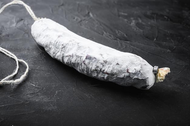 Salchichon, linguiça de salame espanhol na superfície texturizada preta.