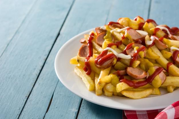 Salchipapa típico da américa latina. salsichas com batatas fritas, ketchup, maionese e mostarda. copie o espaço