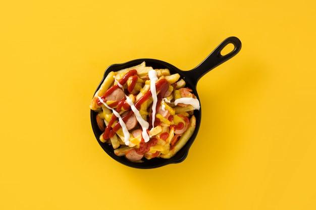 Salchipapa típico da américa latina. salsichas com batatas fritas, ketchup, mostarda e maionese em panela de ferro e fundo amarelo. vista do topo