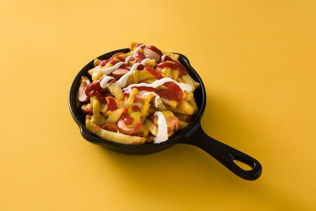 Salchipapa típico da américa latina. salsichas com batatas fritas, ketchup, mostarda e maionese em panela de ferro e fundo amarelo.