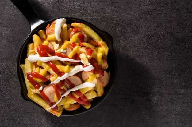 Salchipapa típico da américa latina. salsichas com batatas fritas, ketchup, mostarda e maionese em panela de ferro e fundo preto vista superior espaço para texto